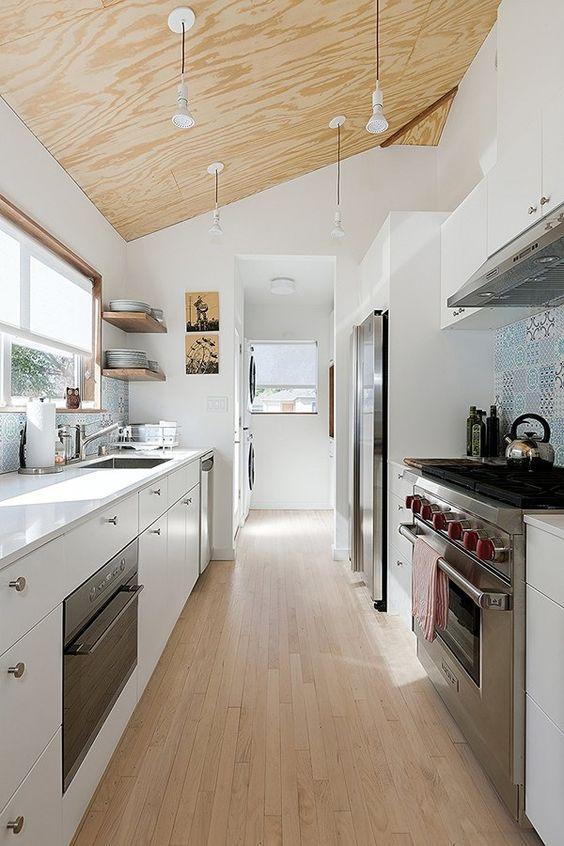 una cucina stretta e lunga moderna con cambusa bianca con soffitto in compensato con lampade a sospensione, pavimento in legno e alzatina piastrellata blu