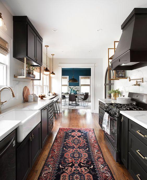 un'elegante cucina stretta e lunga nera con ripiani bianchi e tocchi in ottone più un tappeto stampato e lampade a sospensione vintage