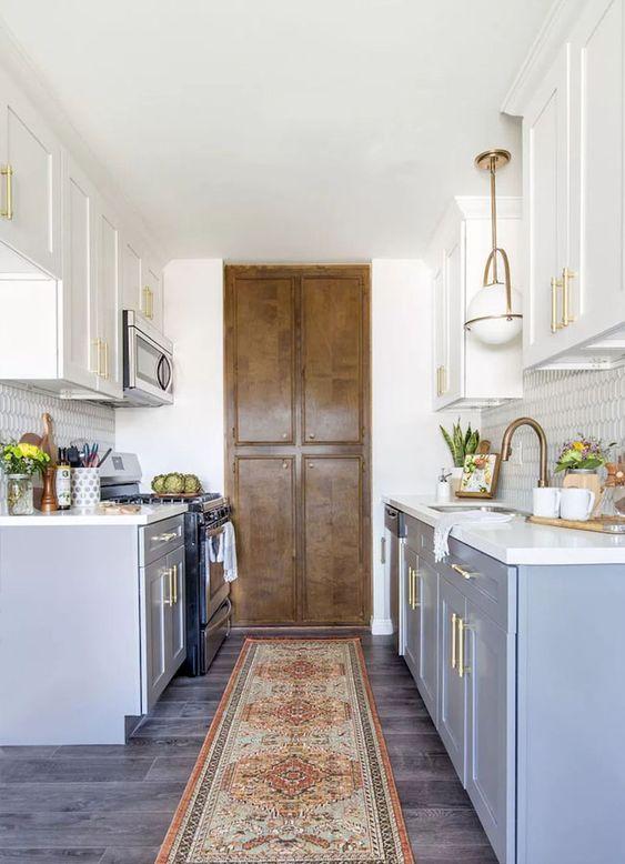 una cucina stretta e corta moderna della cambusa della fattoria in blu con controsoffitti bianchi e tocchi dorati più luci per un look chic
