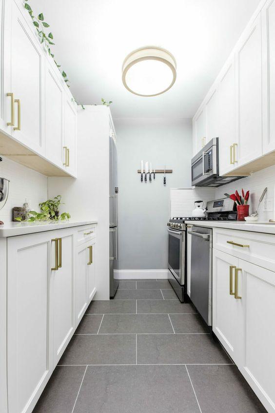 una cucina piccola e stretta moderna della fattoria in bianco con tocchi dorati, un pavimento di piastrelle grigie e una plafoniera è molto elegante e accogliente