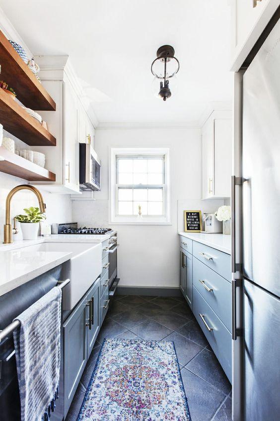 piccola cucina stretta e lunga moderna della fattoria in azzurro e blu navy, con ripiani bianchi, tocchi in ottone e ripiani in legno