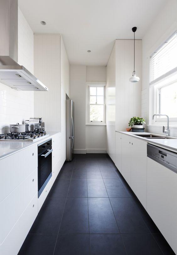 una cucina stretta e lunga bianca minimalista con armadi eleganti, lampade a sospensione e un pavimento in piastrelle nere per un contrasto