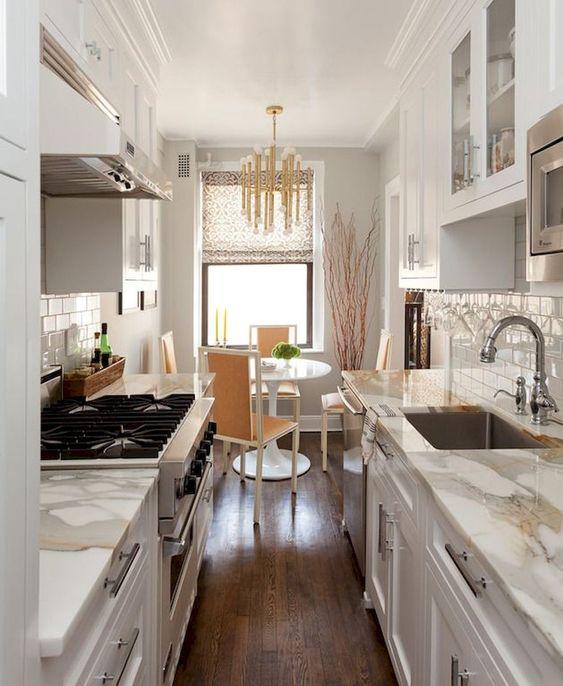 una piccola e accogliente cucina stretta e lunga cambusa con armadi bianchi e ripiani in pietra bianca, un'accogliente sala da pranzo con un tavolo rotondo e un lampadario glam