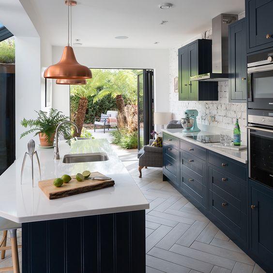 un'elegante cucina con mobili blu scuro e ripiani in pietra bianca, lampade a sospensione in rame e alzatina in mattoni