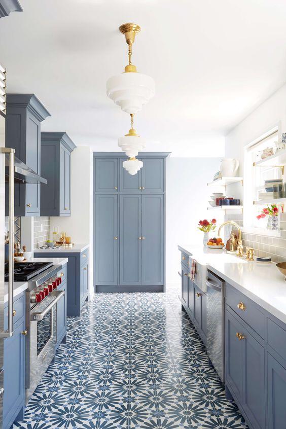 una moderna cucina stretta e lunga da fattoria in blu polvere con pavimento in mosaico, eleganti lampade a sospensione e tocchi dorati per una maggiore eleganza
