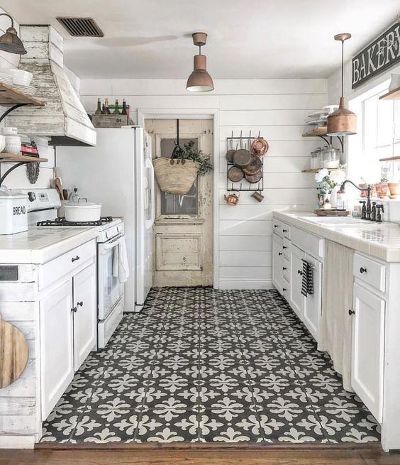 una moderna cucina lunga e stretta in stile rustico con armadi bianchi, hardware blakc, un pavimento a mosaico e una cappa in legno