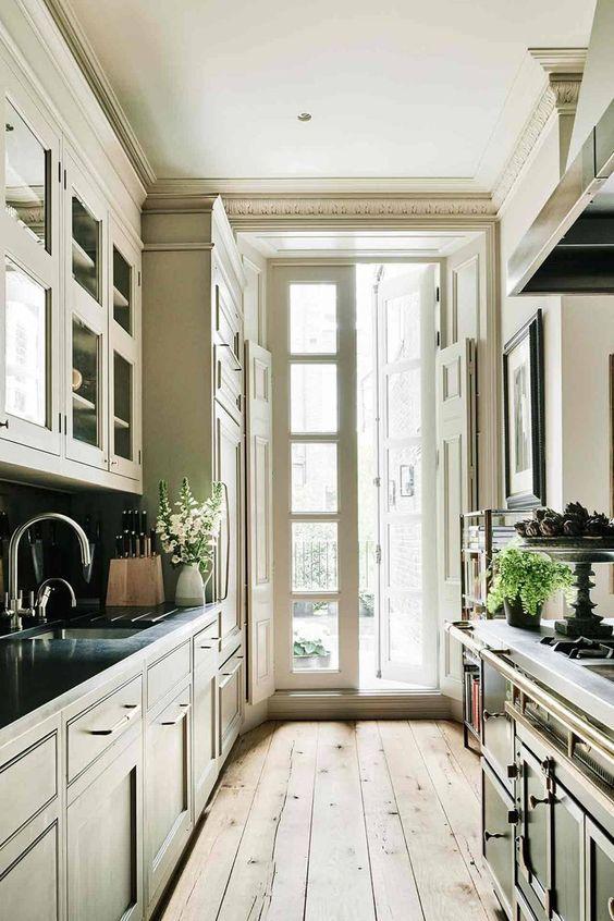 una cucina stretta e lunga tradizionale con armadi scuri vintage, un pavimento in legno, un accesso al balcone con molta luce naturale
