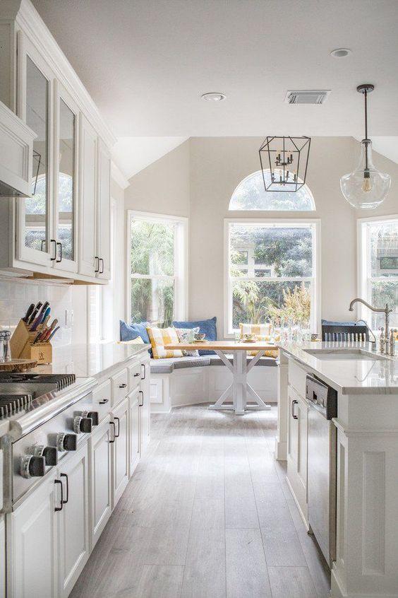 una cucina lunga neutra della cucina della fattoria con armadi chic e ripiani in pietra bianca, pavimento in legno e lampade a sospensione accattivanti
