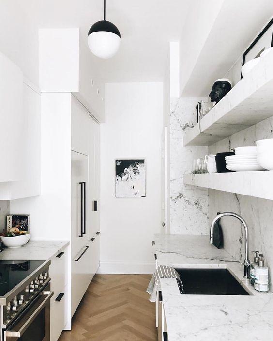 una piccola cucina stretta e lunga scandinava bianca con ripiani in marmo bianco e alzatina più tocchi neri