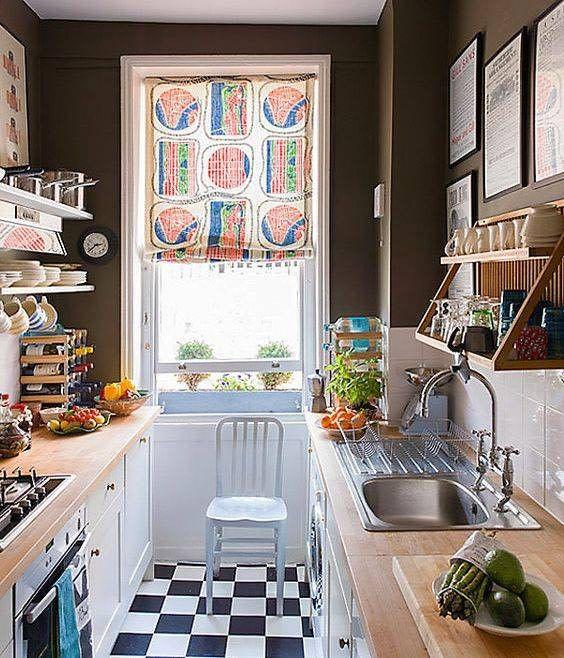 un'eclettica piccola cucina stretta e lunga con pareti nere, un pavimento a quadretti, armadi bianchi con ripiani in blocchi da macellaio e una tenda colorata