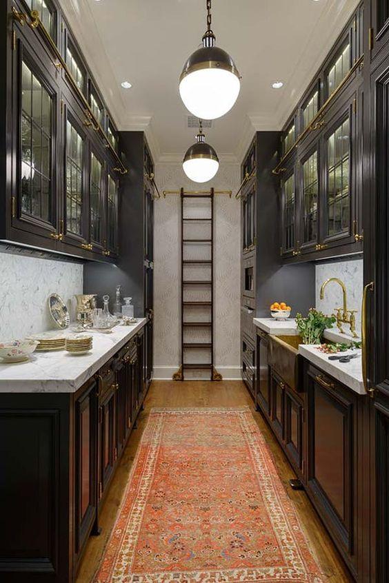 un'elegante cucina lunga scura con tradizionali armadi scuri, una scala per ottenere oggetti da armadi superiori e ripiani in pietra neutra