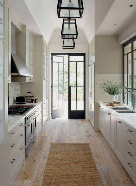 una cucina della cambusa di ispirazione vintage con armadi bianchi, ripiani in pietra bianca e tocchi di blakc per il dramma