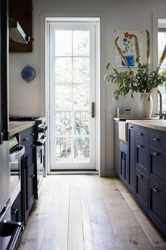 un'accogliente cucina stretta e lunga marina con ripiani in legno, pavimento in legno e molta luce naturale che entra dalla porta