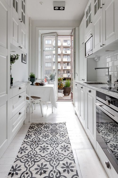 una cucina stretta e lunga scandinava bianca ariosa con armadi bianchi, una piccola sala da pranzo sul balcone e un tappeto stampato