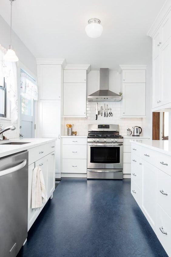 una tranquilla cucina neutra con armadi e ripiani bianchi, un pavimento blu scuro ed elettrodomestici in acciaio inossidabile
