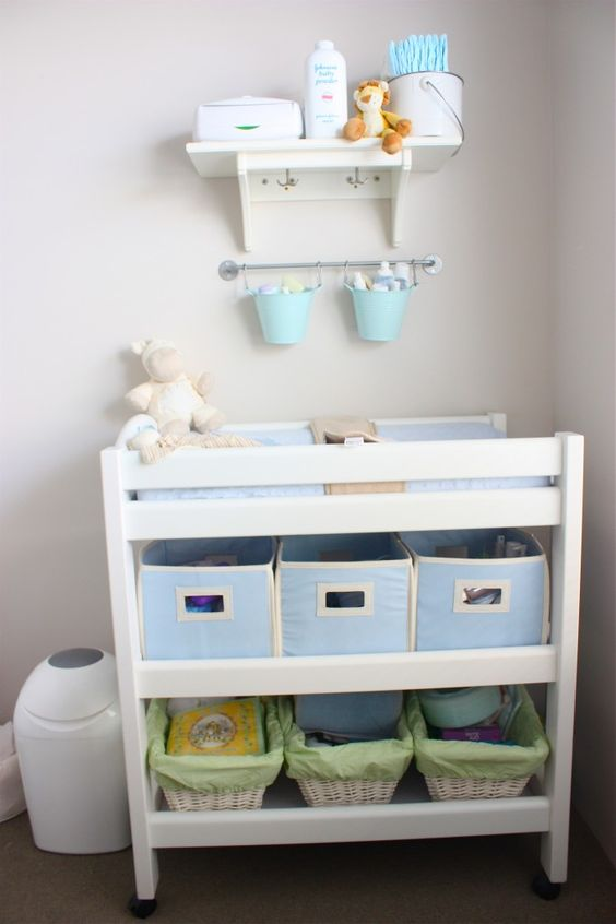 un semplice fasciatoio fatto con scatole di tessuto e cestini come cassetti è un modo facile per organizzare