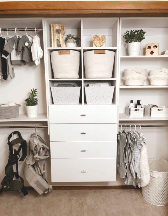 un grande armadio con cassettiera, cesti di stoffa, fioriere e appendiabiti sembra pulito e chic