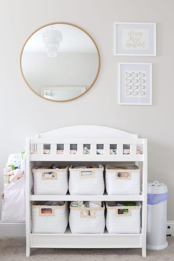 un moderno fasciatoio bianco con cestini in tessuto per organizzare alcune cose e riporle comodamente