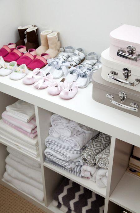 un grande contenitore aperto in bianco e diverse valigie vintage sono un'opzione elegante per organizzare l'armadio di una ragazza
