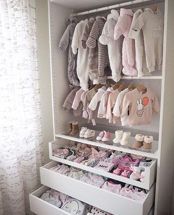 un piccolo e grazioso armadio con vestiti del bambino su grucce, cassetti e un cassetto in vetro con scomparti per organizzare