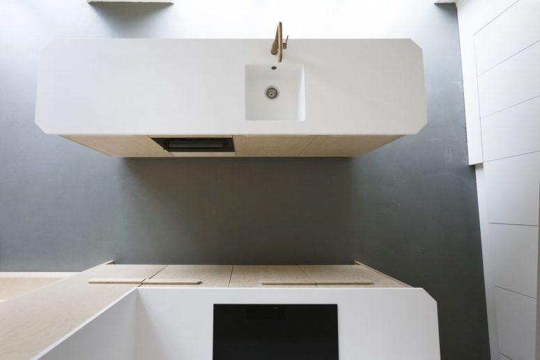 Il pavimento grigio e banconi bianchi completano i mobili in legno chiaro è un modo molto armonioso