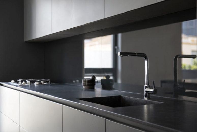 Eleganti controsoffitti in pietra completano l'aspetto laconico ed elegante della cucina