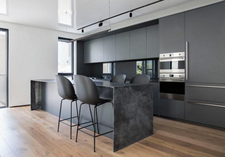 La cucina è realizzata con armadi grigio opaco, un'isola cucina in marmo grigio, sedie nere opache e un alzatina in vetro