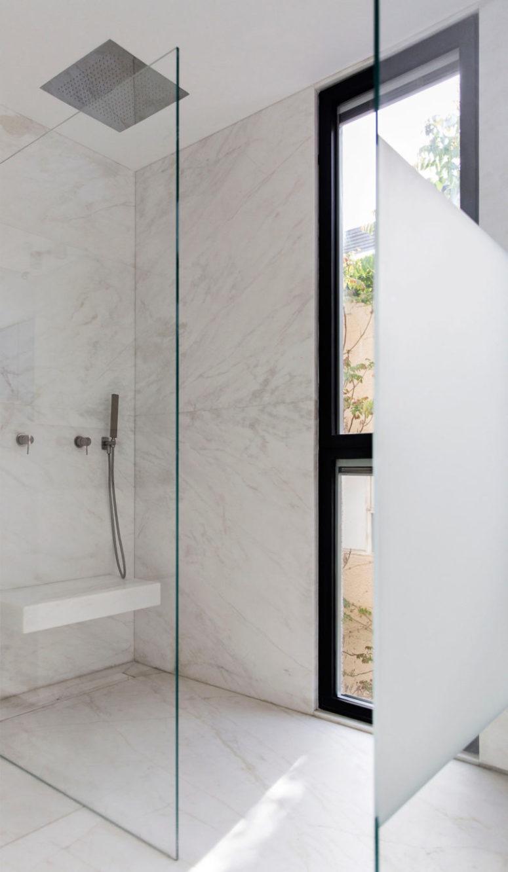 Il bagno è minimalista, realizzato in marmo bianco, con una doccia senza soluzione di continuità e una finestra dal pavimento al soffitto per una vista e molta luce
