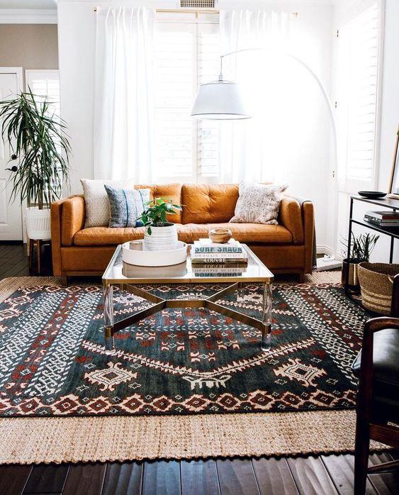 un divano color ruggine è posto davanti ad una delle finestre e non impedisce alla luce di entrare all'interno