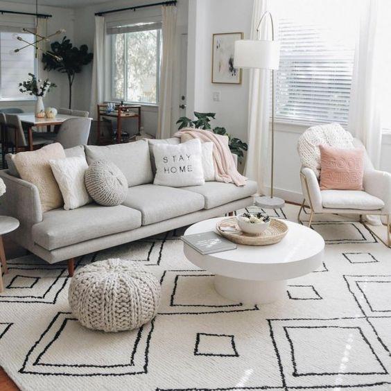 un soggiorno luminoso con un divano bianco e cuscini non è solo un centrotavola ma anche un divisorio tra il soggiorno e la cucina