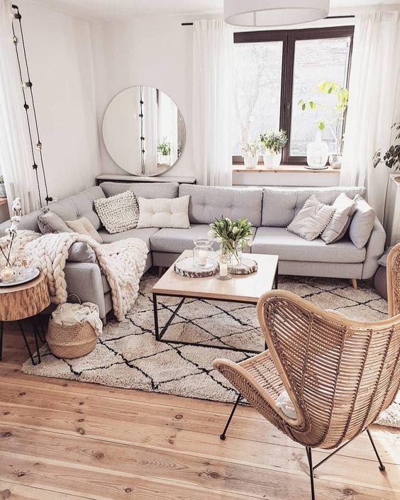 un grande divano componibile grigio posto davanti alla finestra e tutti i mobili disposti intorno ad essa