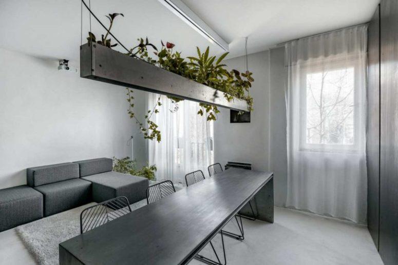 Lo spazio abitativo continua lo spazio con un divano geometrico laconico e piante in vaso