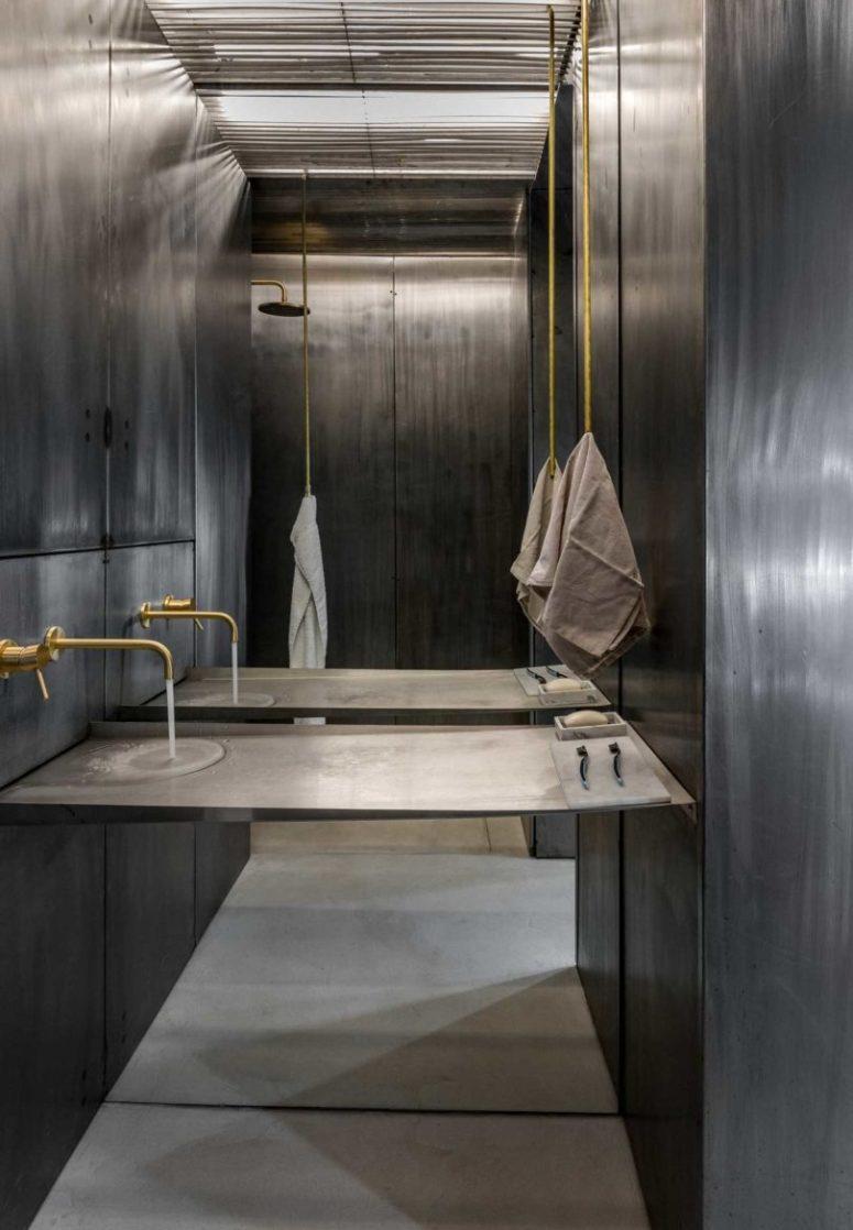 Anche il bagno è rivestito in metallo invecchiato, c'è l'hardware dorato, con una console senza lavabo separato e un vano doccia