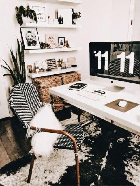 un ufficio boho in bianco e nero con un tappeto astratto, una scrivania e scaffali bianchi, una sedia in rattan e cestini per riporre gli oggetti