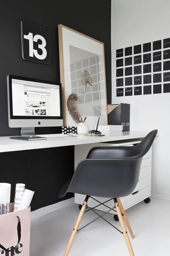 un laconico ufficio a casa nordico con un muro e una sedia neri, un tabellone nero, una scrivania bianca e un'opera d'arte rilassata