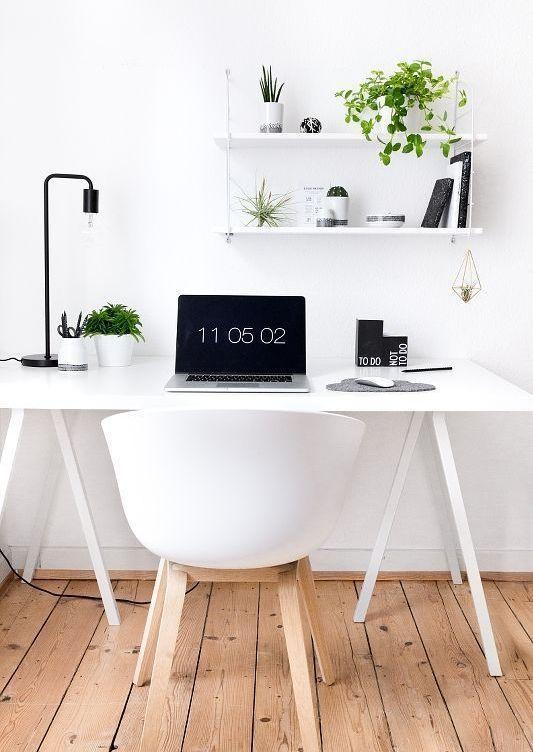 un ufficio da casa nordico in bianco, accentuato con alcuni tocchi neri e una lampada da tavolo nera più verde per rinfrescare lo spazio