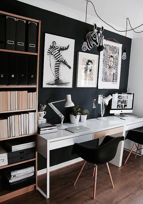 un ufficio da casa contemporaneo lunatico con una parete nera, una scrivania bianca, opere d'arte e uno scaffale