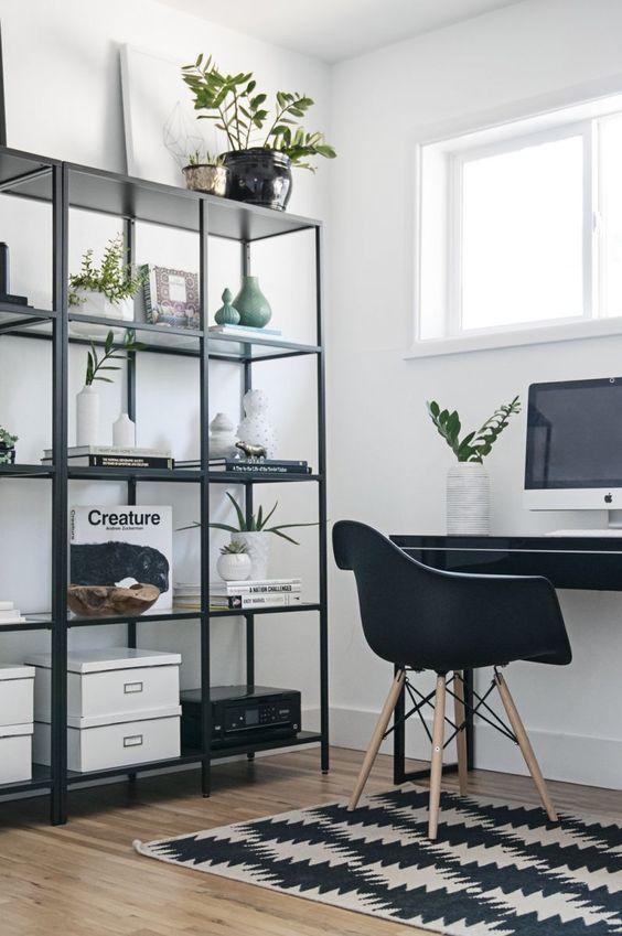 un ufficio in bianco e nero nordico con un tappeto stampato, uno scaffale nero e una scrivania più una sedia