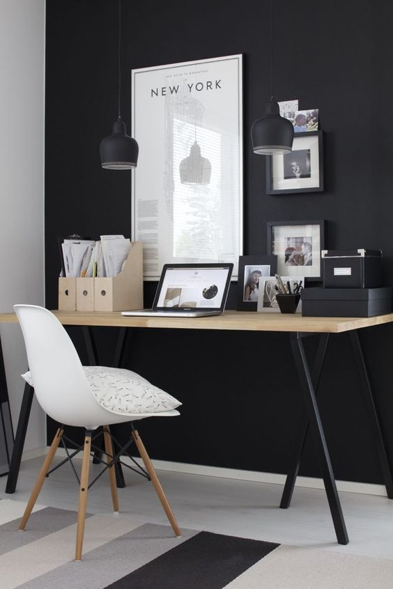 un ufficio da casa lunatico con un muro nero, lampade a sospensione, una scrivania con gambe nere e opere d'arte con cornice nera