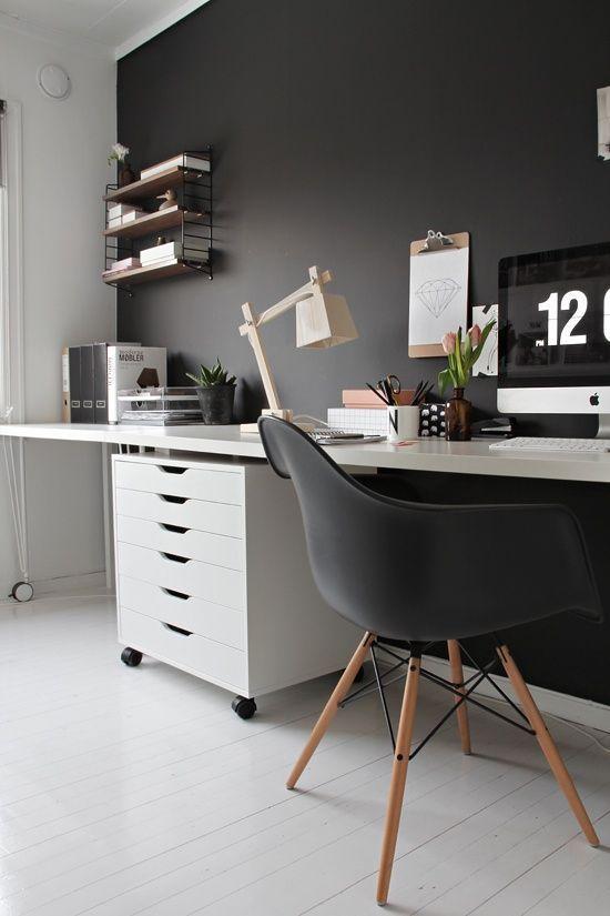 un lunatico ufficio in casa Scandi con una parete nera, una sedia e un arredamento sobrio e bianco come base