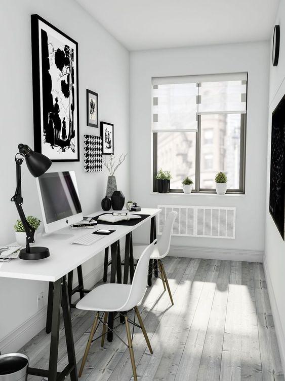 un piccolo ufficio scandinavo con due scrivanie su cavalletto in bianco e nero, sedie bianche e opere d'arte in bianco e nero