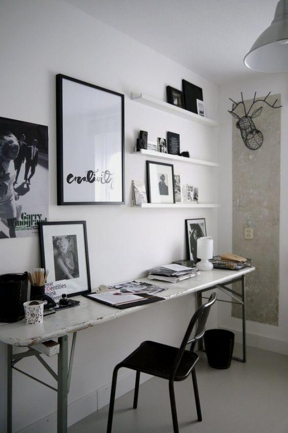 un piccolo ufficio in bianco e nero con una scrivania shabby chic, una sedia nera, opere d'arte e scaffali