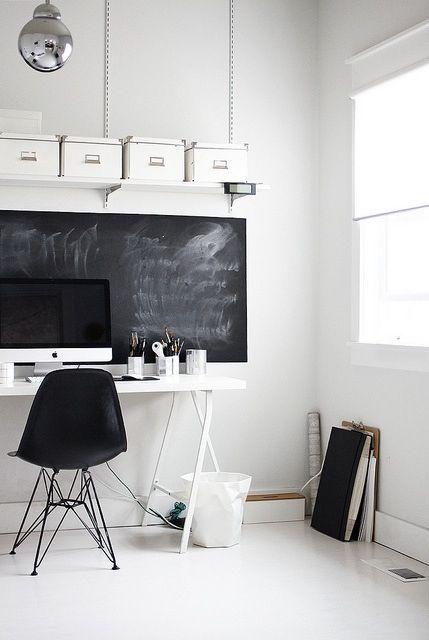 un elegante ufficio eclettico con una lavagna, una scrivania bianca, una sedia nera e alcune scatole bianche per la conservazione