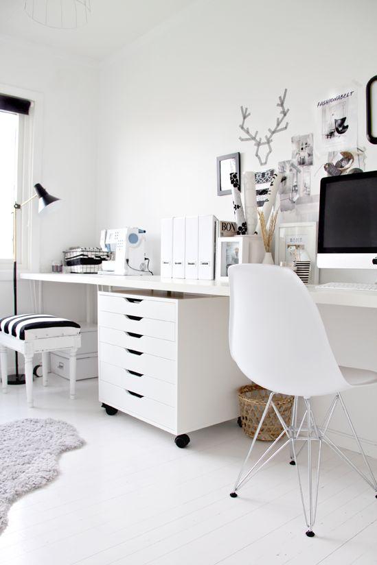 un eclettico ufficio in bianco e nero con mobili bianchi, una lampada nera, cornici per opere d'arte e uno sgabello con seduta a strisce