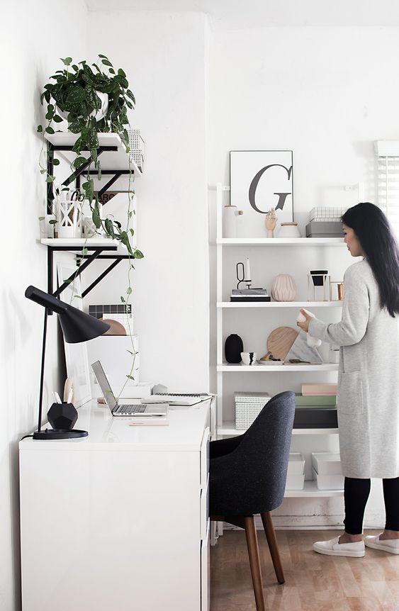 un elegante ufficio a casa contemporaneo in bianco, con una sedia nera, lampada, mensole bianche e nere sul muro