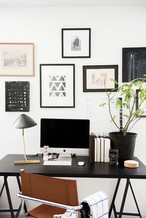 un elegante ufficio in casa scandinavo con una scrivania a trespolo blakc, una sedia in pelle e una galleria a muro in bianco e nero