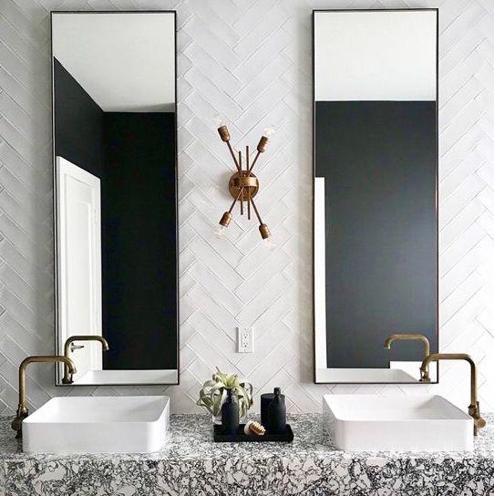 un audace bagno in stile art déco con piastrelle bianche e magre rivestite con un motivo a chevron e una vanità galleggiante in terrazzo
