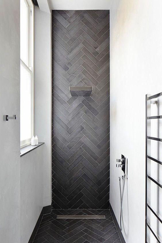 uno spazio doccia elegante e contemporaneo con pareti bianche e un accento grigio grafite piastrelle skinny rivestite in un motivo a chevron ed estese al pavimento