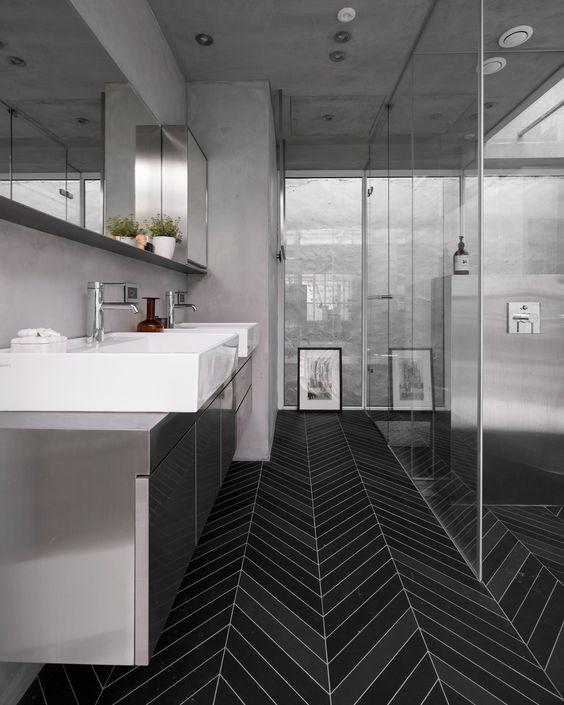 un bagno minimalista con pareti grigie e una vnaity grigia più un accattivante pavimento in piastrelle nere skinny per un contrasto