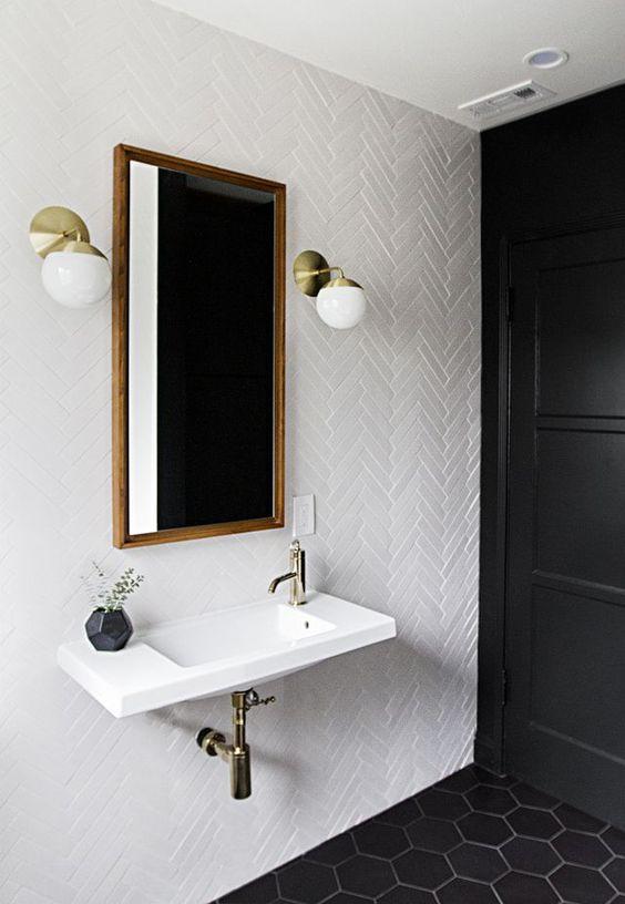 piastrelle bianche sottili in un motivo a cheveron abbinate a piastrelle esagonali nere sul pavimento per un look da bagno chic